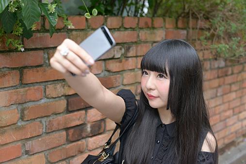 Harajuku woman taking self portrait with smartphon